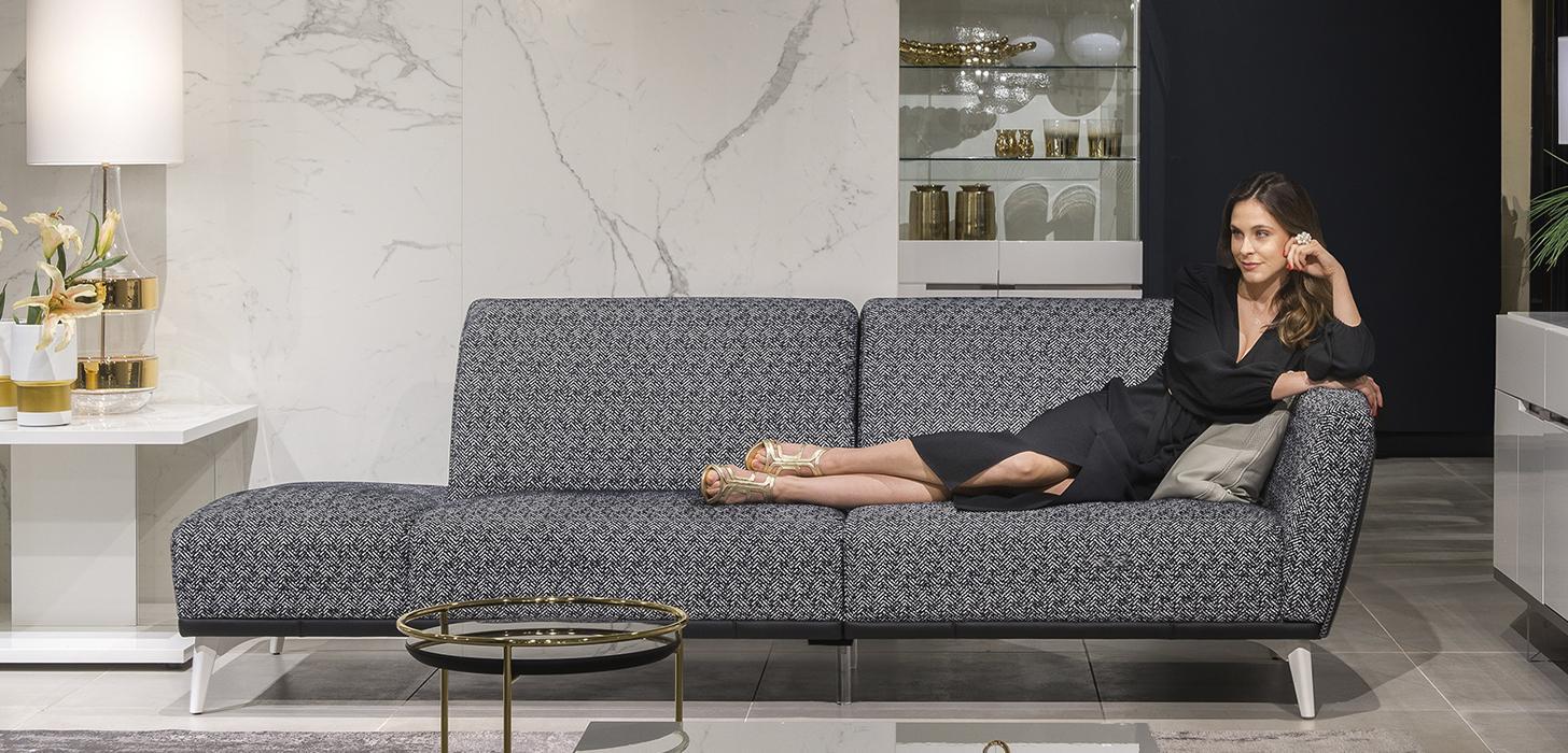 Kobieta siedząca na czarno-białej sofie Gondoliere marki Kler z wysokimi, białymi, nóżkami