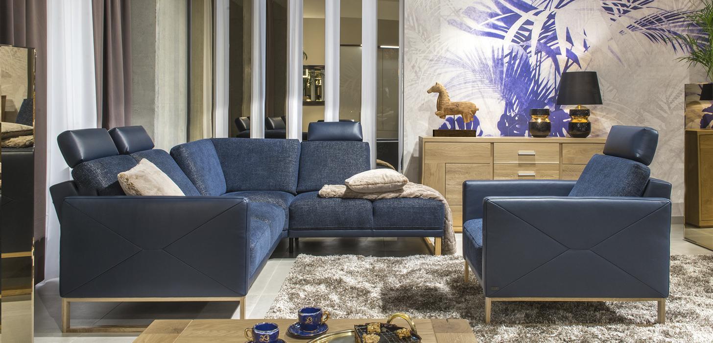 Zestaw mebli Kler Estrada wykonany w połączeniu niebieskiej tkaniny i skóry z drewnianą płozą, umieszczony w eleganckim salonie.