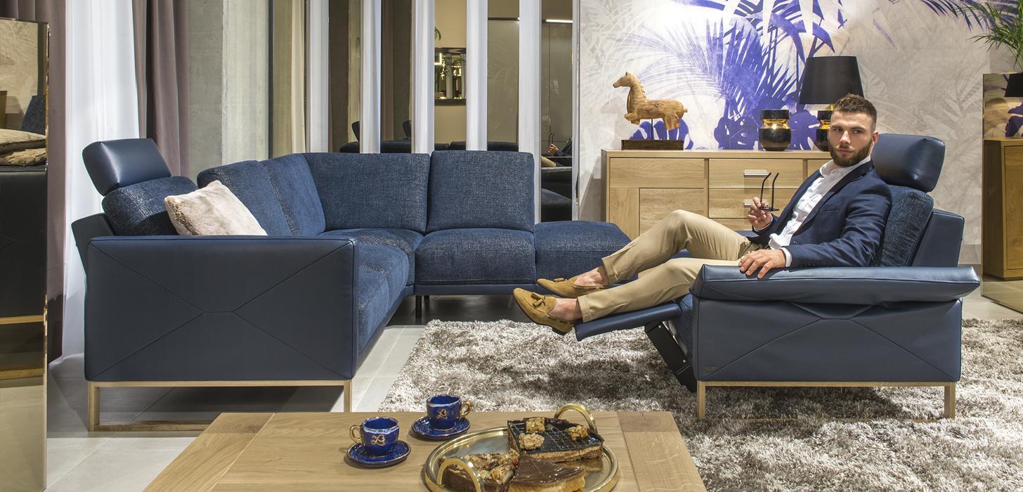 Mężczyzna siedzący w fotelu w salonie. Fotel i narożnik w niebieskim kolorze wykonany w połączeniu skóry i tkaniny z jasną, drewnianą płozą.