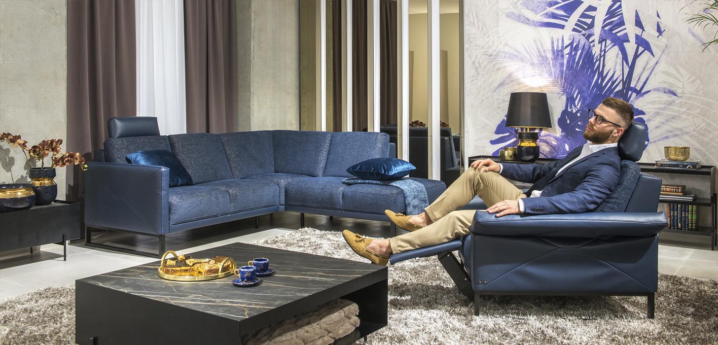 Mężczyzna siedzący w niebieskim fotelu Kler Estrada, niebieski narożnik z kolekcji Estradawykonany w skórze i tkaninie.