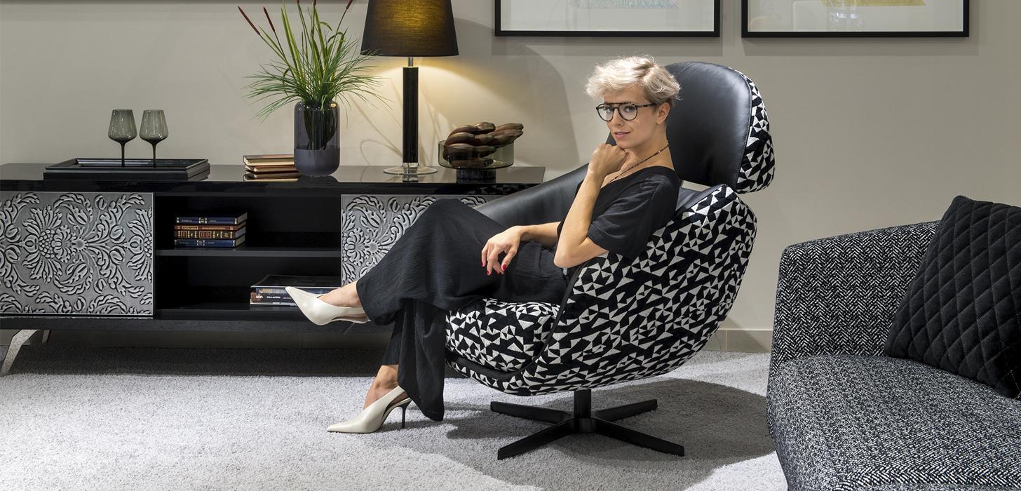 Kobieta siedząca w fotelu Kler Cornetta w czarno - białej odsłonie, w salonie, obok komoda