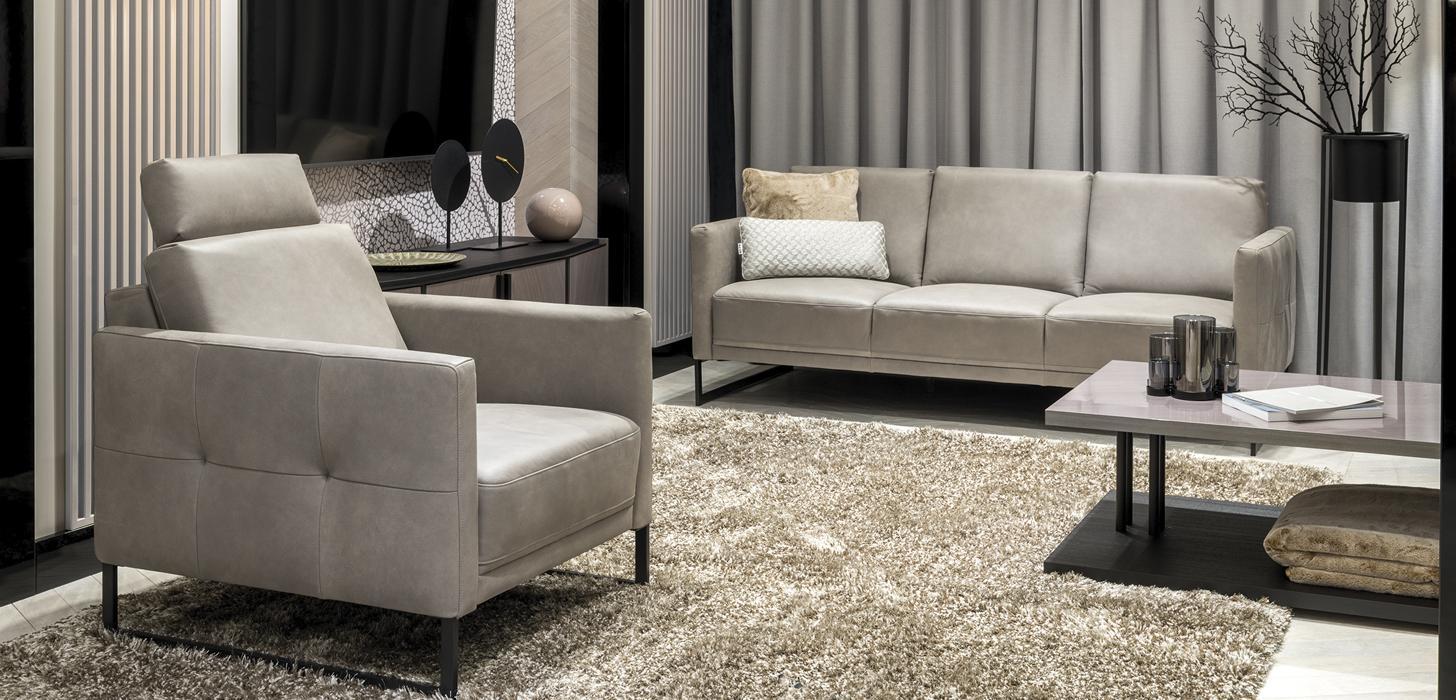 Kolekcja Kler Estrada w szarej skórze z metalowymi, czarnymi płozami. Fotel i sofę z tej kolekcji umieszczono w eleganckim salonie.