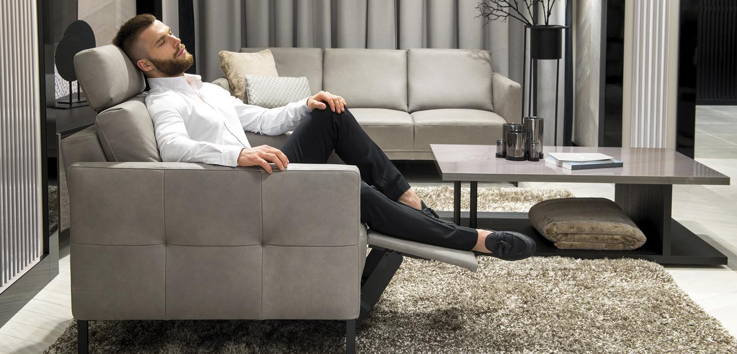 Szary fotel Kler Estrada z metalową czarną płozą z rozłożonym podnóżkiem - wygodne miejsce do odpoczynku.