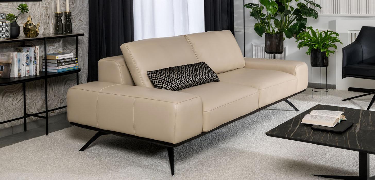 Beżowa sofa Kler Figaro Uno, z czarną poduszką, obok stolik z kamiennym blatem i fotel.