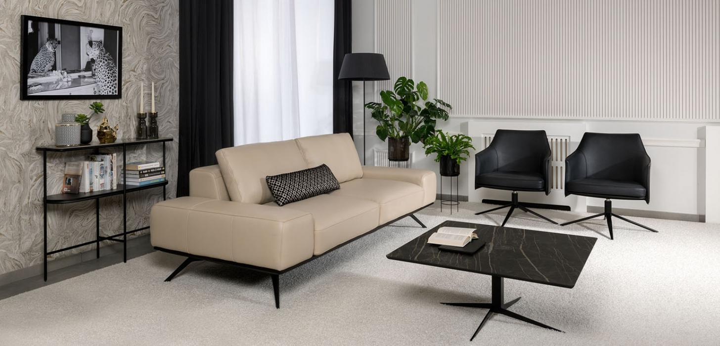 Sofa Kler Figaro Uno w beżowej skórze w otoczeniu prostokątnego stolika z kamiennym blatem i dwóch czarnych foteli.