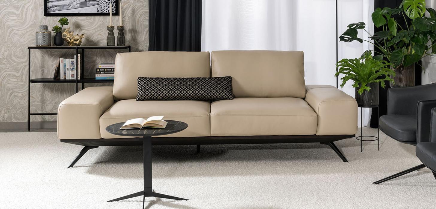 Sofa Figaro Uno marki Kler wykonana w beżowej skórze licowej i czarny stolik z kamiennym, okrągłym blatem stojący przed nią.