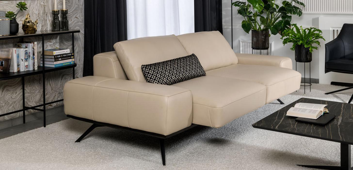 Sofa Kler Figaro Uno z wysuniętym siedziskiem, stojąca w salonie przy ciemnym, kamiennym stoliku.