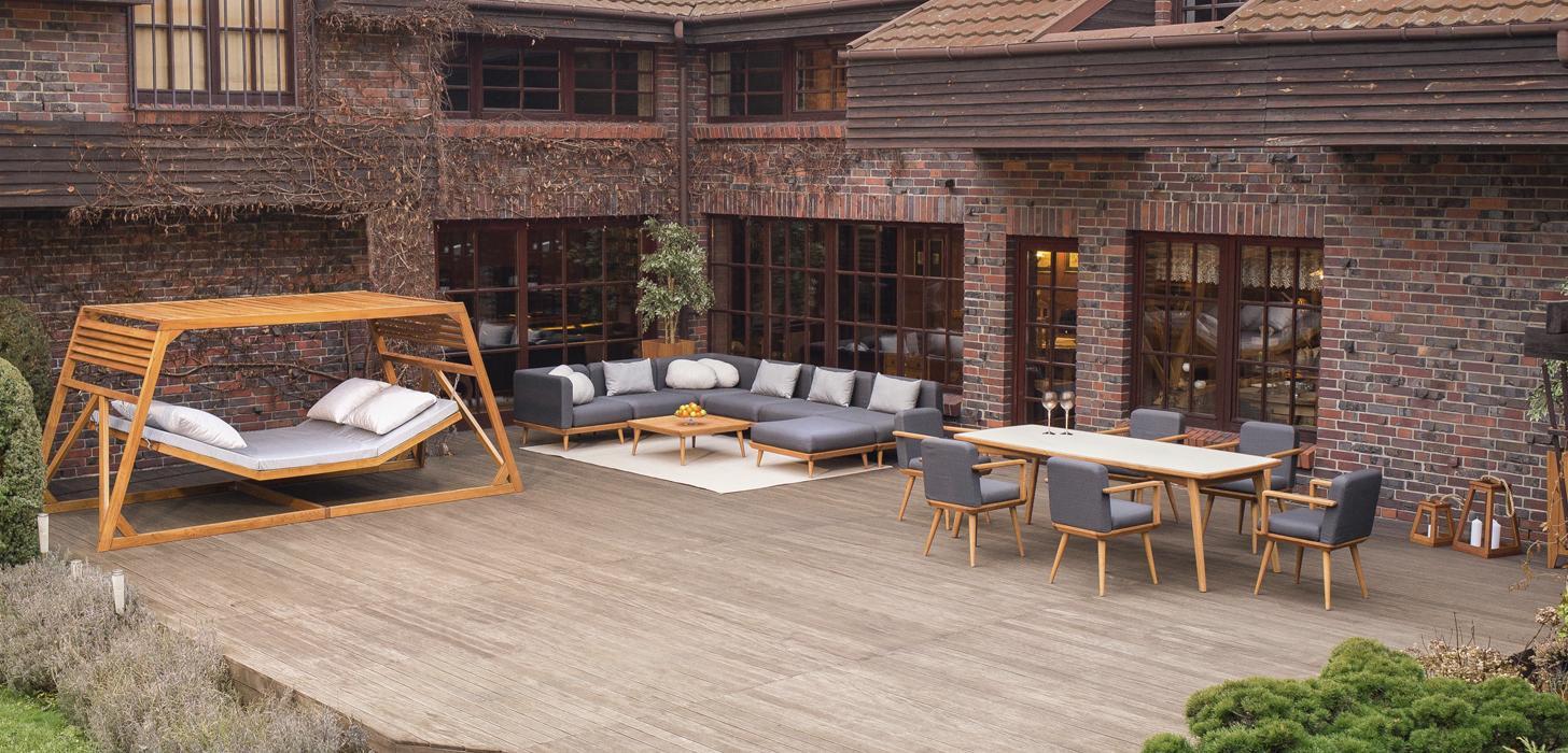 Kolekcja mebli ogrodowych Nourd, drewniana konstrukcja, szare tapicerowane siedziska i oparcia. Kolekcja dostępna w salonach Kler.