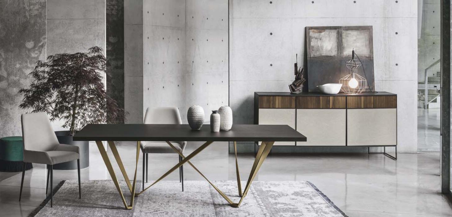 Szare, tapicerowane krzesło Havana z oferty Kler, w towarzystwie stołu z brązowym blacie na złotej podstawie Wave oraz komody Vinci. Całość w pięknej, nowoczesnej aranżacji.