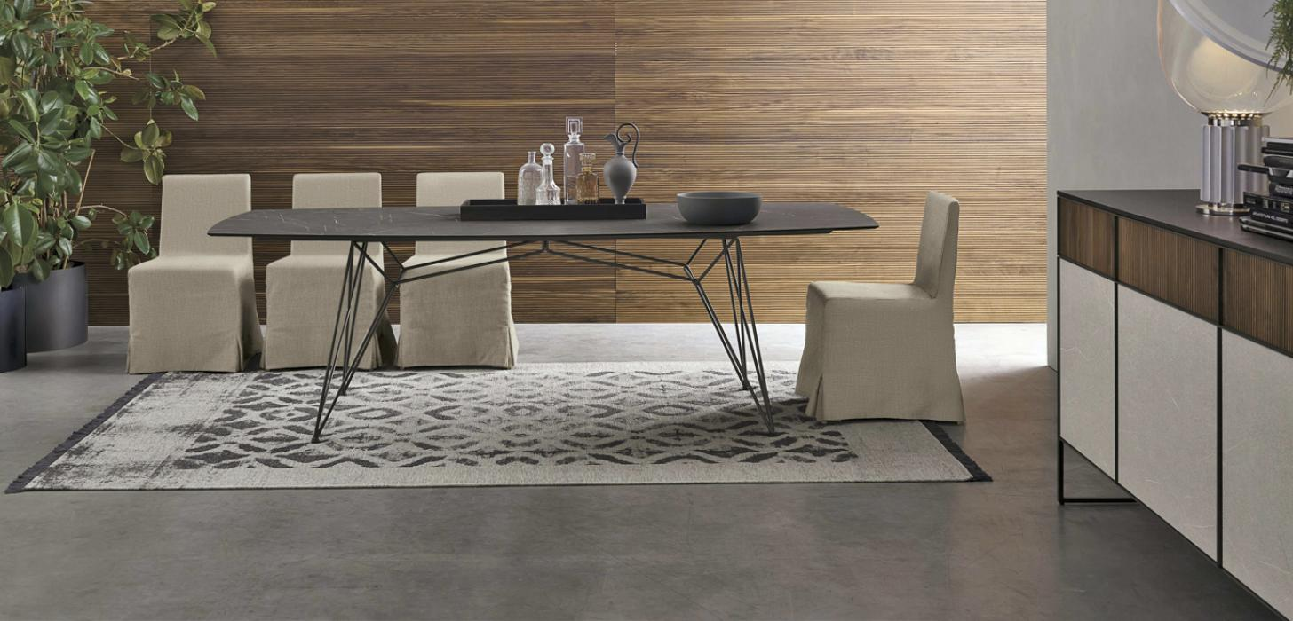 Aranżacyjne zdjęcie wnętrza ze stołem Wave z oferty Kler. Stół stoi na metalowej podstawie. Blat w ciemnym kolorze. Oprócz stołu znajdują się krzesła, komoda Vinci oraz rośliny.