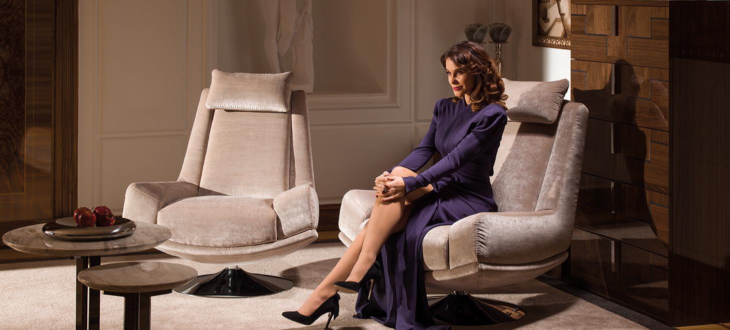 Kobieta siedząca w eleganckim fotelu Kler Andante w beżowym kolorze.