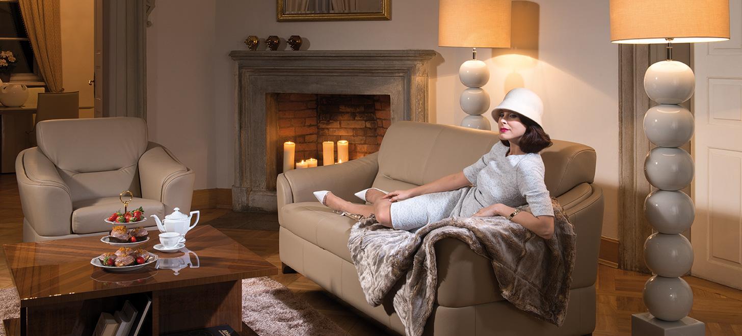 Elegancka kobieta siedzącana beżowej sofie Arpeggio marki Kler, w tle kominek i świece.