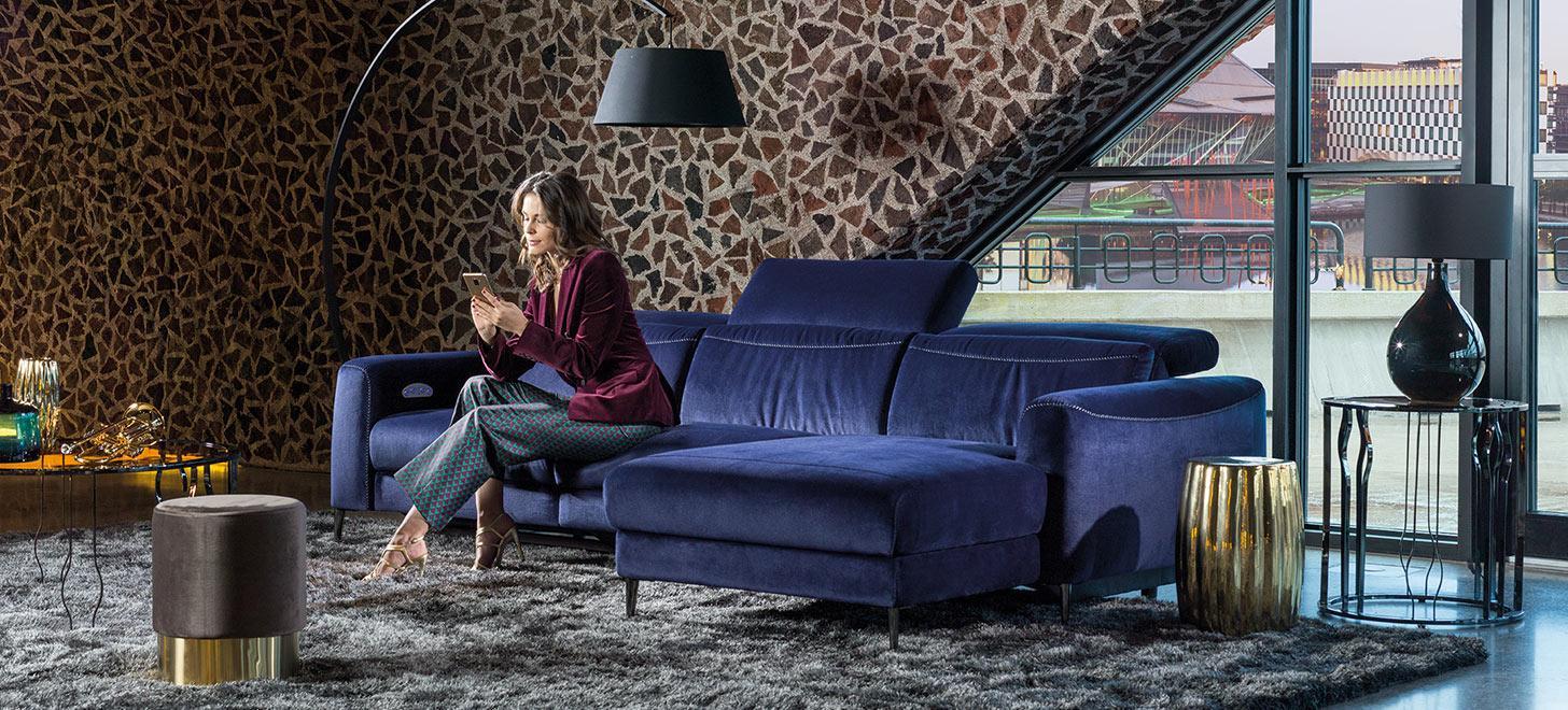 Narożnik w niebieskiej tkaninie - Capriccio z oferty Kler - w nowoczesnym salonie z przeszkleniem.