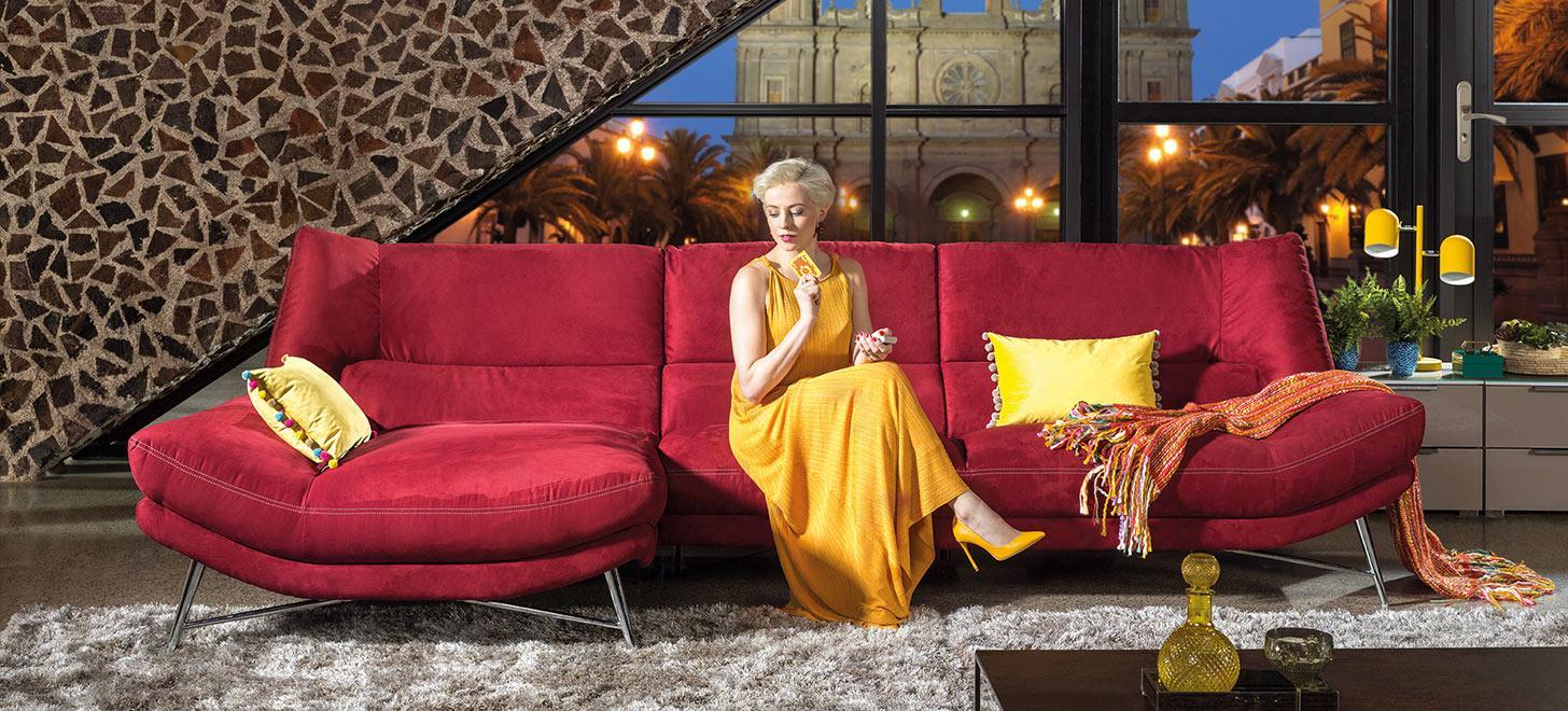 Kobieta w żółtej sukience na czerwonej kanapie wykonanej w tkaninie. Obok żółte poduszki. Kolekcja Kler Carmen.