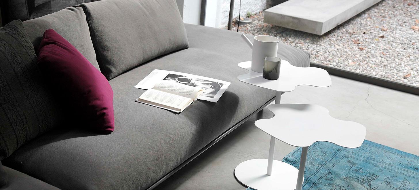 Dwa, białe, metalowe stoliki Flower firmy Bontempi z oferty Kler. Stojące przy szarej kanapie na niebieskim dywanie.
