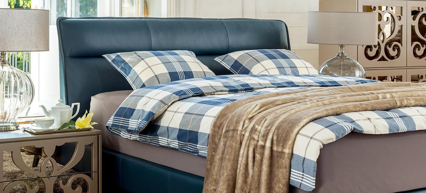 Zbliżenie na łóżko kontynentalne Balletto firmy Kler tapicerowane skórą w kolorze niebieskim, z imponującym wezgłowiem. Przykryte pościelą w niebiesko białą kratę. Obok łóżka stoi stolik nocny i komoda z kolekcji Ornamento Kler.