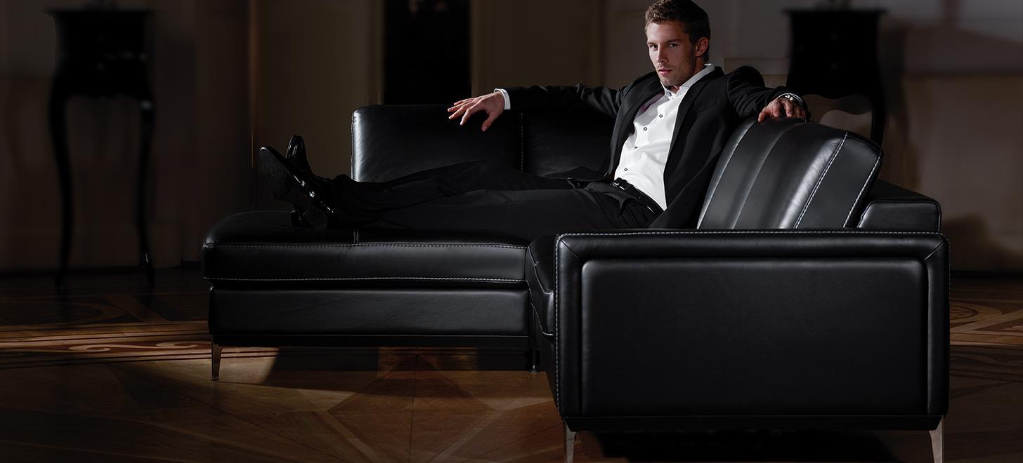 Mężczyzna siedzący na czarnym narożniku Kler Can-Can