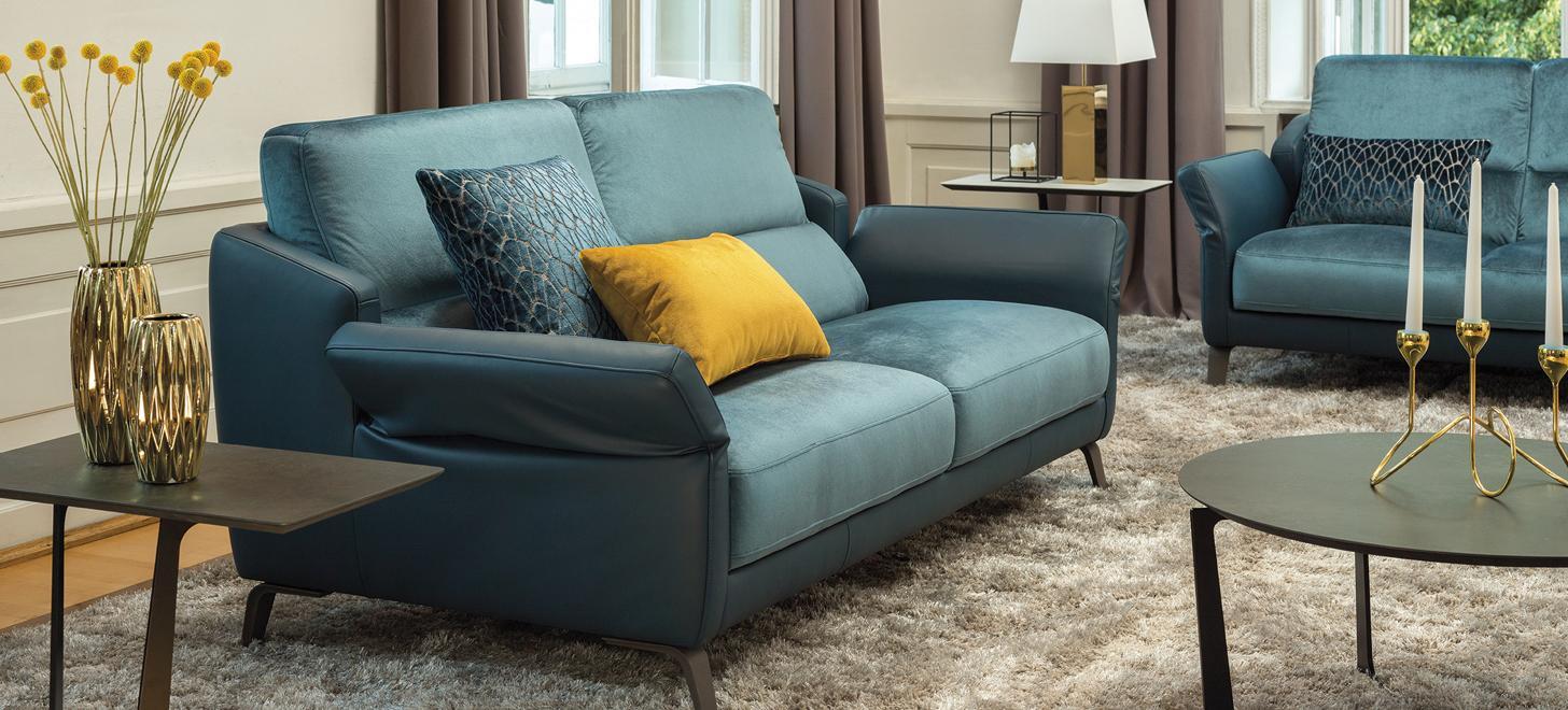 Elegancka sofa w niebieskiej tkaninie w środkowej części i niebieskiej skórze na zewnętrznych elementach - kolekcja Kler Diva