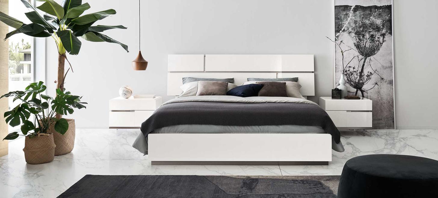 Eleganckie łóżko, z imponującym wezgłowiem formatu grande, z metalowymi rowkami wraz z szafką nocną z kolekcji Artemide z oferty Kler.
