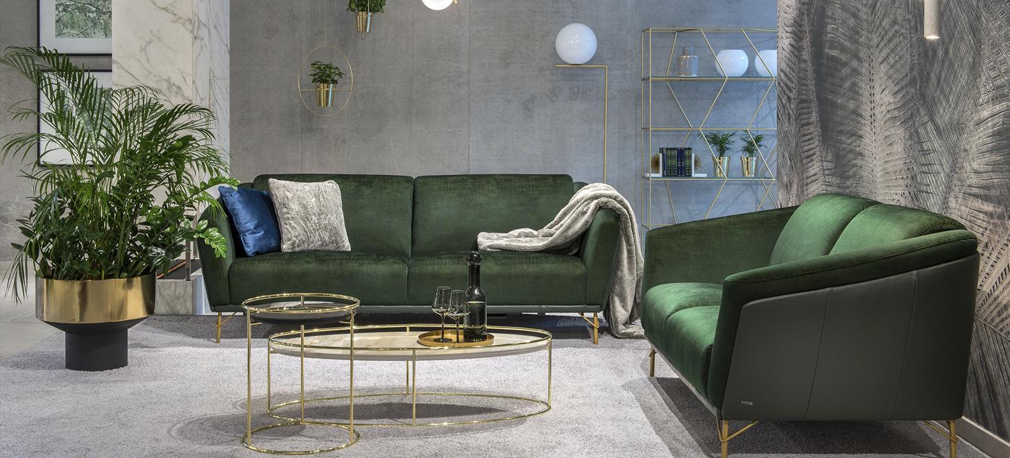 Wykonany z połączenia zielonej skóry i tkaniny zestaw mebli Gondoliere marki Kler, składający się z dwóch sof, z wysokimi, złotymi nóżkami.