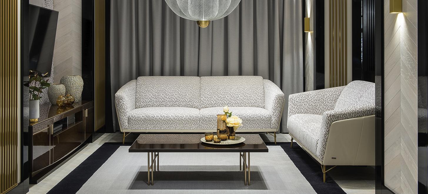 Kolekcja mebli Kler Gondoliere składająca się z 2 sof na wysokich złotych nóżkach, w jasnych odcieniach, ustawiona w sąsiedztwie brązowej komody RTV i brązowego stolika kawowego