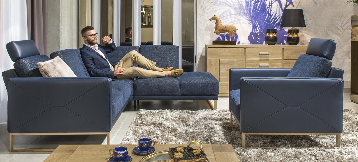 Mężczyzna wypoczywający na narożniku Kler Estrada w niebieskim kolorze. Zestaw złozony z narożnika i fotela Kler.