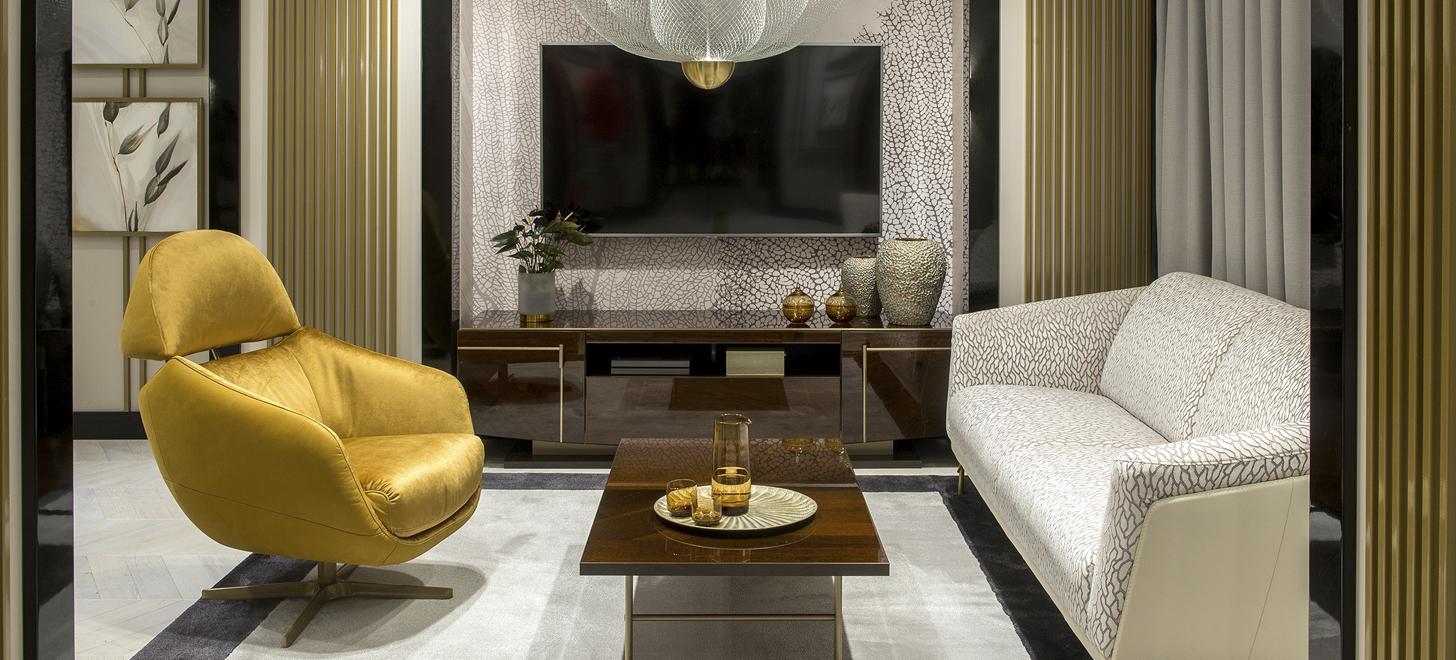 Złoty fotel Kler Cornetta na przeciw sofy Gondoliere marki Kler, w salonie.