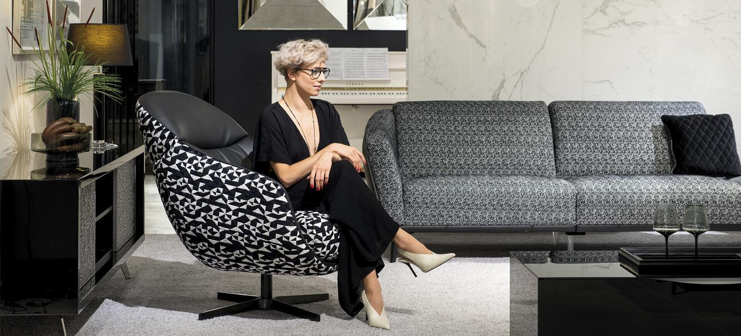 Kobieta siedząca w czarno-białym fotelu Kler Cornetta, w tle sofa Gondoliere z oferty Kler