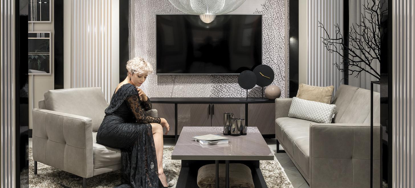 Kolekcja Estrada - zestaw mebli składający się z fotela i sofy w szarej skórze i siedząca w fotelu kobieta.