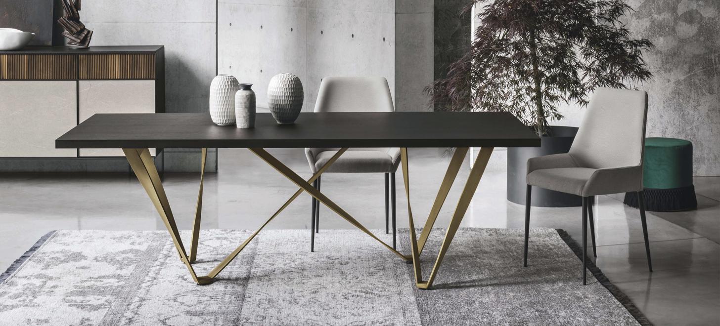 Tapicerowane, szare krzesło Havana z oferty Kler. Obok stół z brązowym blatem na złotej podstawie Wave oraz komoda Vinci. Całość w pięknej, nowoczesnej aranżacji. W tle roślina i zielona pufa.