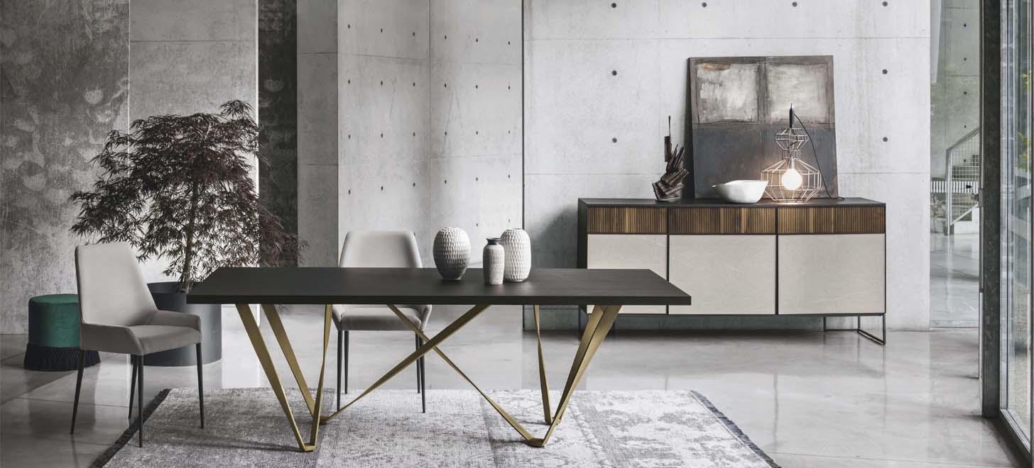Stół Wave z oferty Kler z ciemnym blatem, na złotej podstawie. W towarzystwie stołu krzesła Havana i komoda Vinci. Na komodzie piękne elementy dekoracyjne.