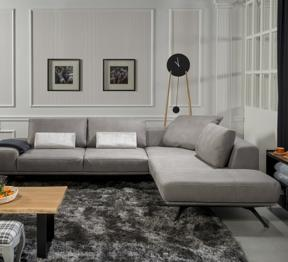 Zdjęcie szarego narożnika Figaro Due w salonie, obok nowoczesny zegar i stolik z drewnianym blatem - elegancki salon z meblami marki Kler.